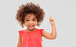 Leinwanddruck Bild - idea, warning and childhood concept - happy little african american girl pointing finger up over grey background