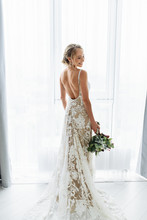 Awesome Bride In A Long Wedding Dress With A Beautiful Bouquet In Hand And With Charming Smile