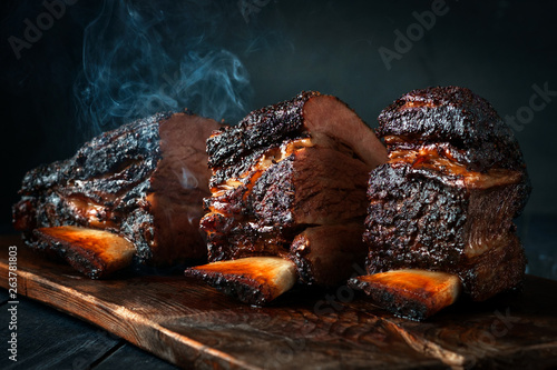 Canvas Cut a large piece of smoked beef brisket to the ribs with a dark crust