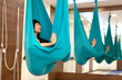Woman meditation in hammock. fly yoga stretching exercises in gym. Fit and wellness lifestyle