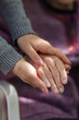 Young caregiver holding seniors hand. Elderly concept