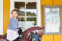 A Young Girl Riding On A Toy Horse In Front Of A Small Town Store.