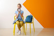 canvas print picture - Portrait of cute teenage girl with megaphone sitting on chair near color wall