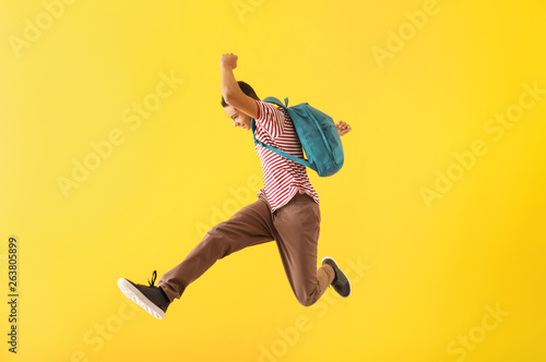 Foto  Portrait of jumping African-American teenage boy on color background