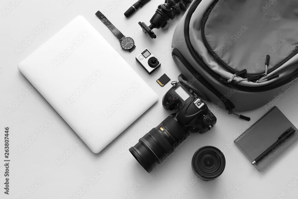 Fototapeta Modern equipment of professional photographer with laptop on light background - obraz na płótnie