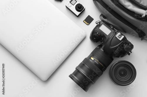 Fotomural  Modern equipment of professional photographer with laptop on light background