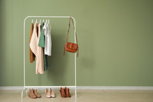 Rack With Stylish Clothes Near Color Wall