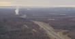Smoke rises over highway in Alaska, wide aerial