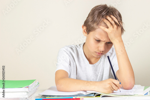 Fototapeta Sad boy doing homework. Education, school, learning difficulties concept obraz
