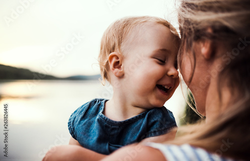 Fotografie, Obraz  Smiling mother holding toddler outdoors