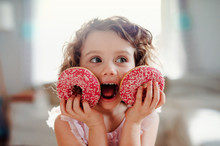 A Small Girl With Doughnuts At Home, Looking At Camera.