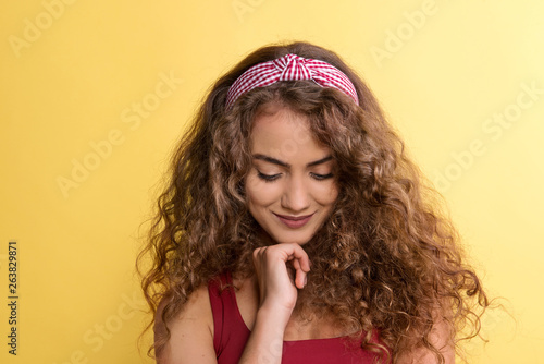 Valokuvatapetti Portrait of a young woman with headband in a studio on a yellow background