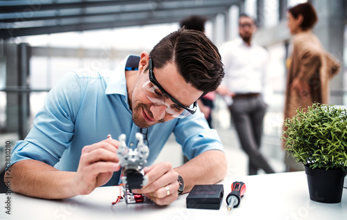 Cuadros en Lienzo A young businessman or scientist with robotic hand standing in office, working