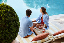 Couple Relaxing With Wine Pool...