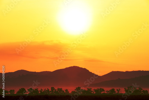 Foto auf AluDibond Gelb Picture of a sun setting behind a dense forest area followed by mountains.