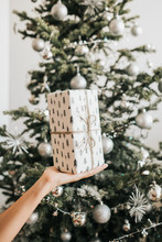 Girl Holding A Gift Wrapped On The Background Of A Decorated Christmas Tree