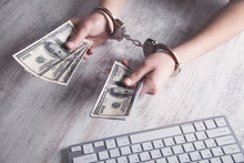 Hands In Handcuffs With Money. Cyber Crime Concept