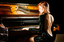 Charming Girl In Evening Dress Posing Near The Old German Piano. Back View.
