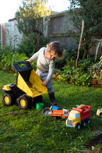 Boy Playing With Toy Dump Truck In Back Yard, New Zealand.