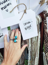 Hand Wearing Turquoise Ring Next To Written Note.