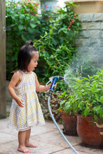 Happy Little Asian Girl Playing With Water Tap In The Garden