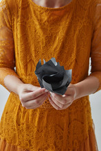 The Girl In An Orange Dress Hold Hanmade Black Paper Flower In Her Hand. Halloween Colors Concept.
