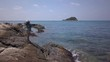 Aerial: a tracking shot around a beautiful young thai woman standing at a rocky shore near the ocean rising her arms in the air and smiling while the drone rotates around her, Thailand.