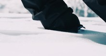 Close Up Of Snowboarder Boots Walking In Soft Fresh Powder Snow