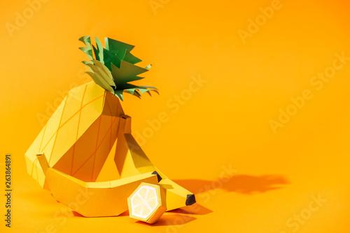 Photo  handmade paper pineapple, bananas and lemon on orange with copy space