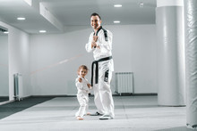 Smiling Caucasian Taekwondo Trainer Posing With Little Girl In White Gym.