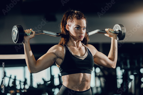 Attractive Caucasian female bodybuilder with ponytail lifting barbell while standing in gym Canvas Print