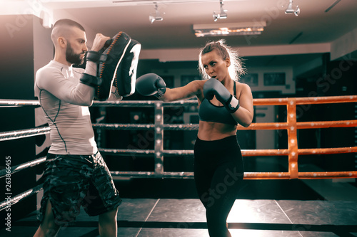 Cuadros en Lienzo  Strong muscular boxer Caucasian woman punching and having training in ring