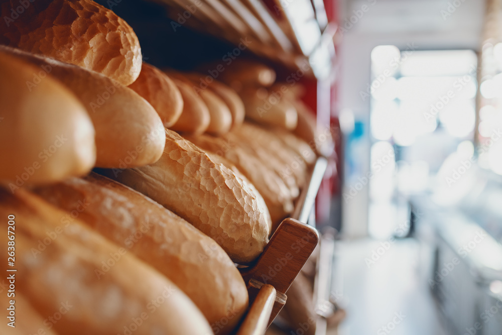 Fototapety, obrazy: Close up of fresh delicious loafs of bread in row on shelves ready for sale. Bakery interior.