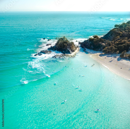 Photographie Aerial shot at sunrise over the ocean and white sand beach with swimmers and sur