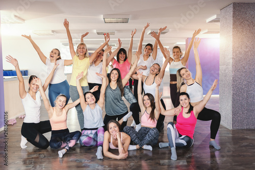 Fototapeten Tanzschule Cheerful sporty group of Caucasian women posing in gym. In background mirror. Dedicate yourself to becoming your best.