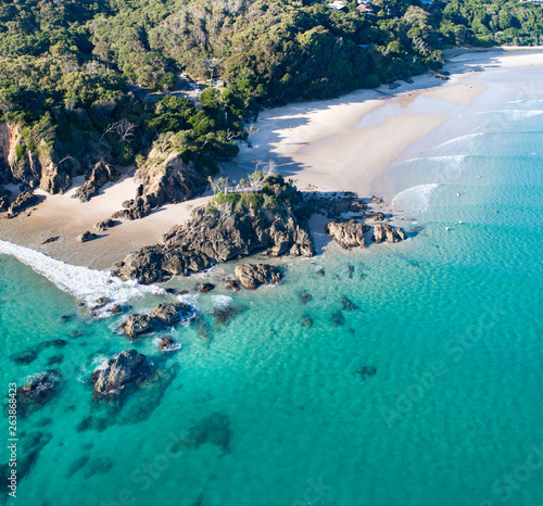 Tela Aerial shot at sunrise over the ocean and white sand beach with swimmers and sur