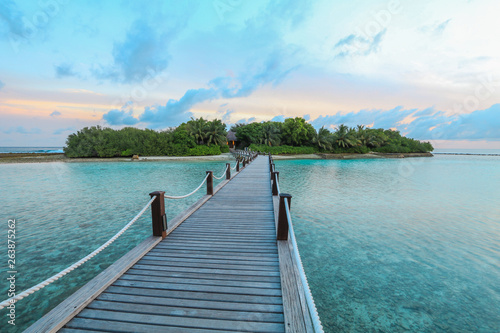 Fotografia  Amazing island in the Maldives ,wooden bridge and  beautiful  turquoise waters with  blue sky  background for holiday vacation
