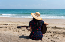Girl Playing Guitar On The Beach