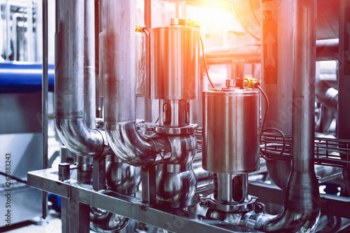 Stainless steel brewing equipment, reservoirs or tanks and pipes and pipelines in modern beer factory. Brewery production concept, abstract industrial background
