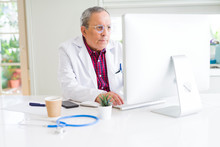 Senior Doctor Man At The Clinic Concentrated Working With Computer Looking For A Cure
