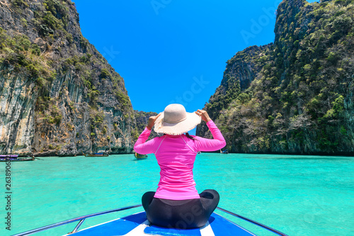 Photo  Young woman sitting at the front of boat in Maya Bay on Phi Phi Leh Island, Krabi Province, Thailand