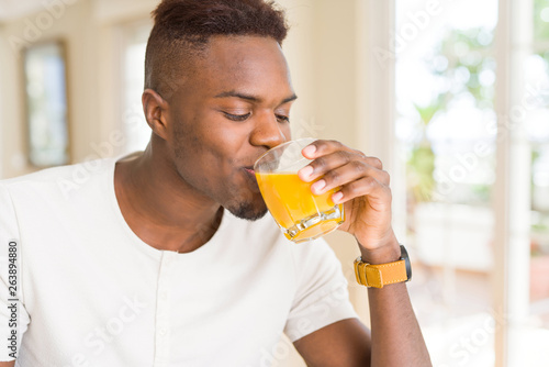 Photo Stands Juice Handsome young african man drinking a glass of fresh natural orange juice enjoying fruit refreshment
