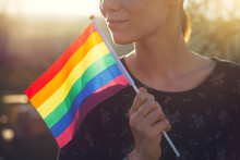 Happy Young Smiling Woman With Rainbow Ribbon Wristband On Her Hand Holding Lgbt Colorful Rainbow Flag Next To Her Face, Morning Sunshine, Outdoor