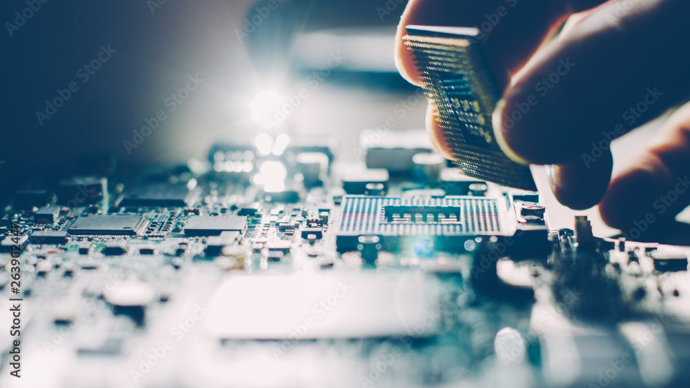 Fototapeta Engineer plugging CPU microprocessor to motherboard socket. Computer technology and hardware maintenance or repair.