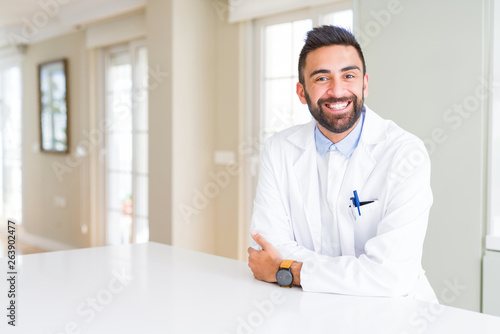 Fotografia, Obraz Handsome hispanic doctor or therapist man wearing medical coat at the clinic happy face smiling with crossed arms looking at the camera