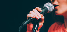 Singer At Microphone. Woman Singing And Holding Mic. Female Vocal Talent. Music Show Recital.
