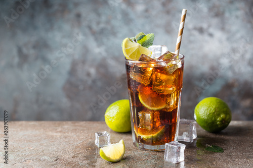 Fresh made Cuba Libre with brown rum, cola, mint and lemon on gray stone backgro Canvas Print