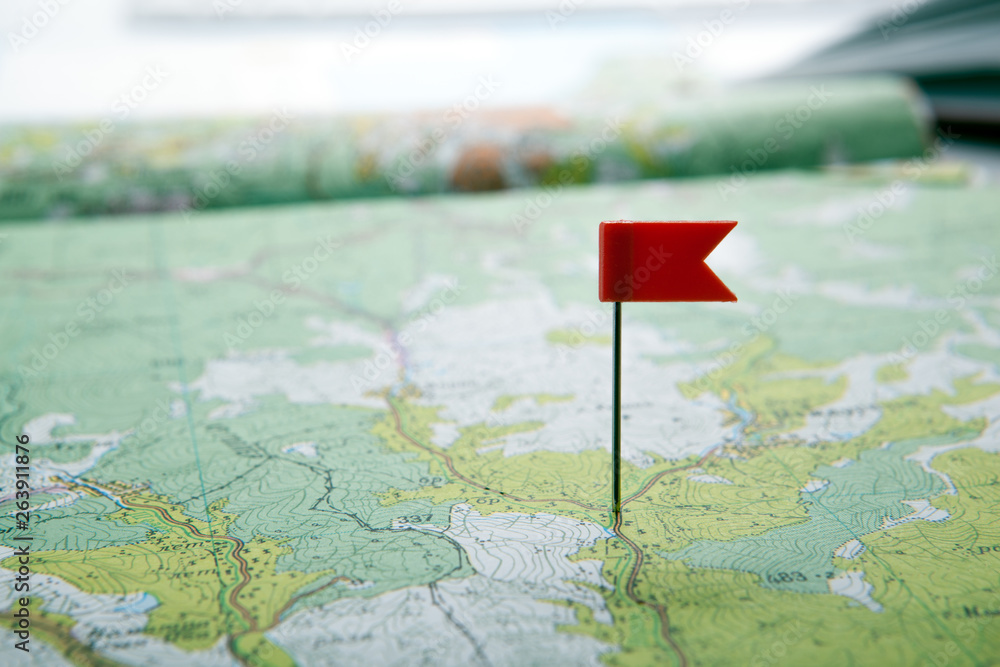 Fototapeta topographic map with colored flag pushpin close up