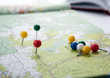 canvas print picture - topographic map with colored needles pushpins close up