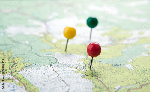 Fotografia  topographic map with colored needles pushpins close up